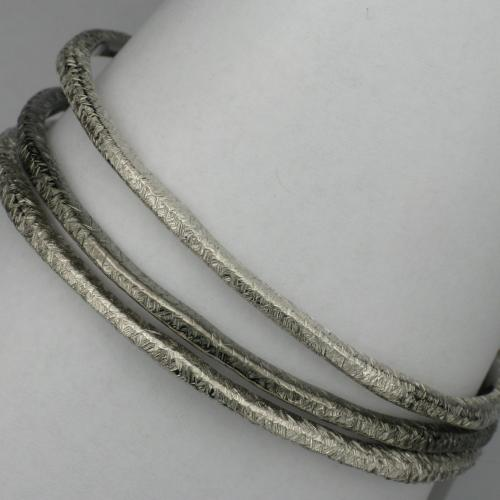 Set of three sterling silver bangle style bracelets with textured finish.